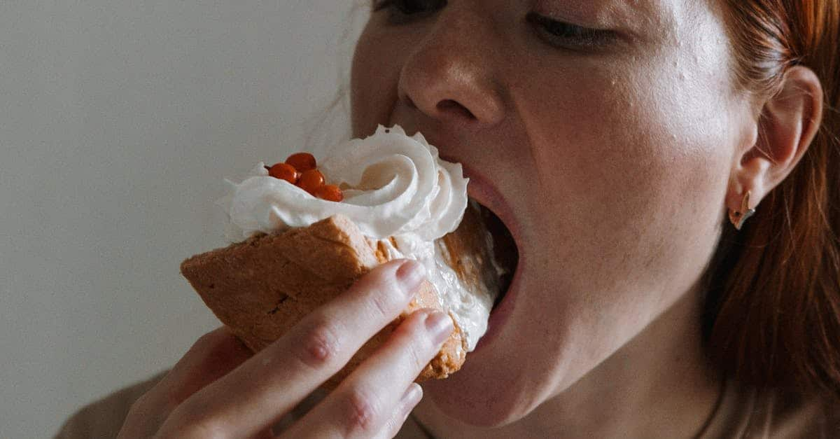 A close up of a person eating a sandwich