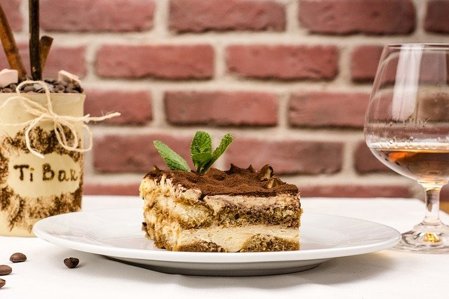 A piece of cake on a plate next to a glass of wine